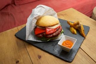 rica hamburguesa con pimiento rojo y queso grana padano sobre una cama de canónigos y salsa romescu